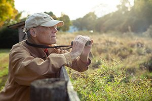 Senior living resident is birdwatching at sunset in the meadow