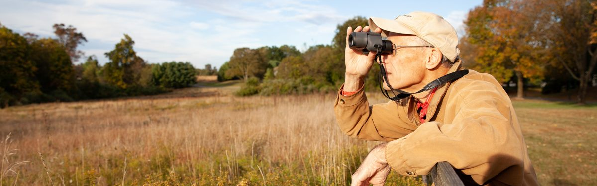 Resident enjoys birdwatching in the picturesque meadow on the White Horse Village campus