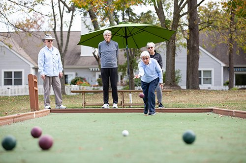 group of residents play an exciting match of bocce ball outdoors