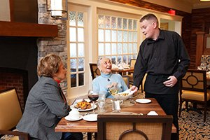 A server chats with residents about the delicious food and drink