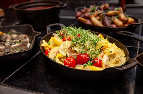 Iron skillets full of colorful and healthy vegetables in the Paddock Grille