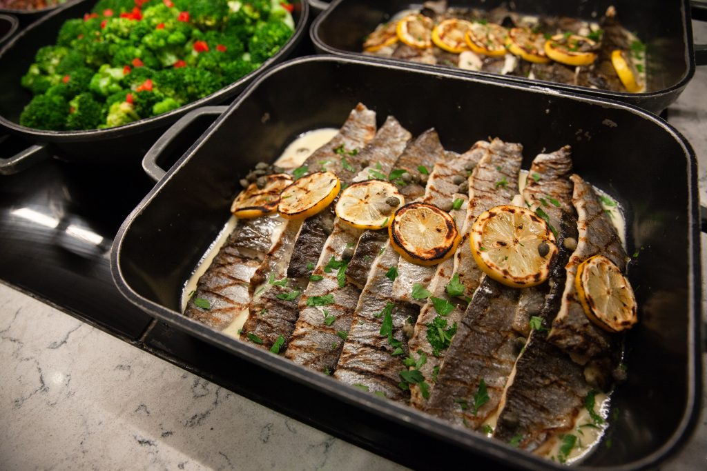 Flavorful buffet featuring an array of meals including sautéed fish and vegetables