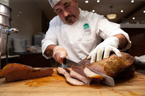 Expert chef carving a mouthwatering ham for carving night