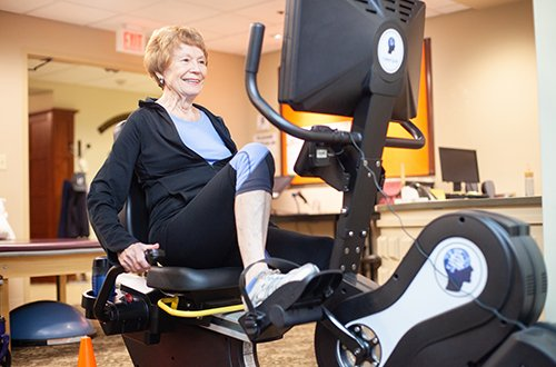 Resident exercise on an incumbent bike in the Fitness Center at White Horse Village