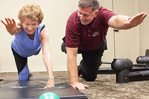 Resident and trainer do floor exercises in the Fitness Center