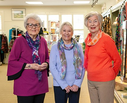 Three women resident volunteers standing in the gift shop