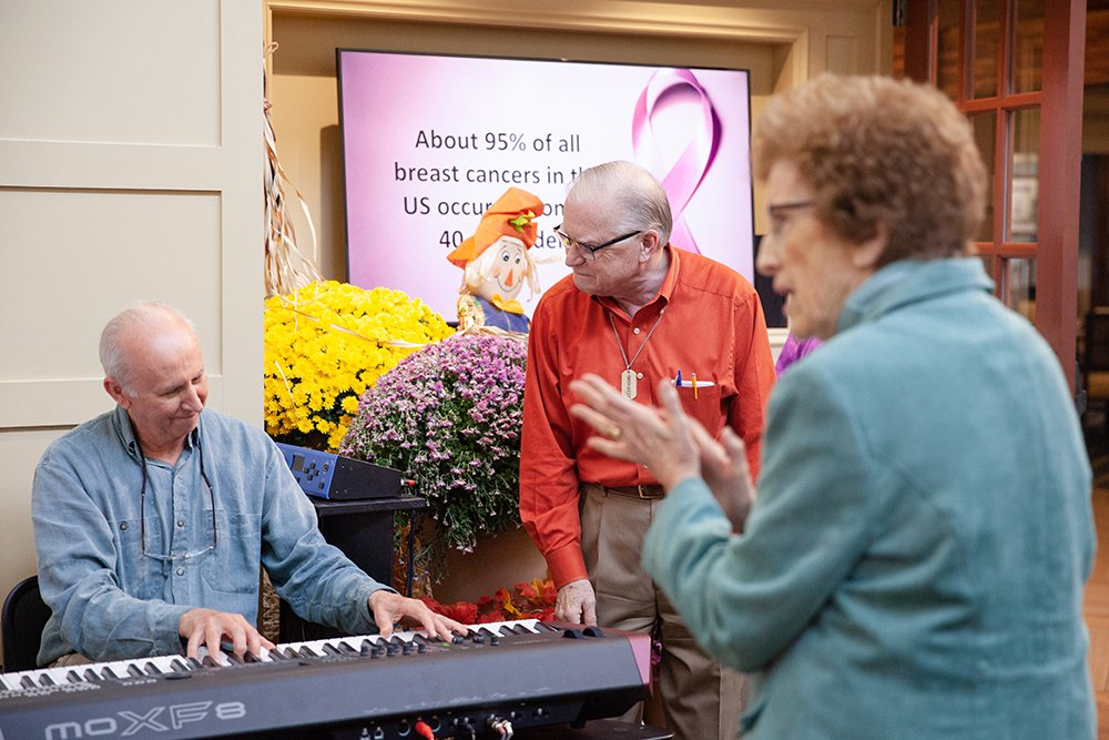 Residents enjoy a piano sing along before dinner