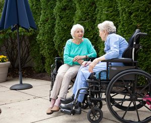 Two healthcare residents enjoying a conversation on the outside patio of the healthcare center