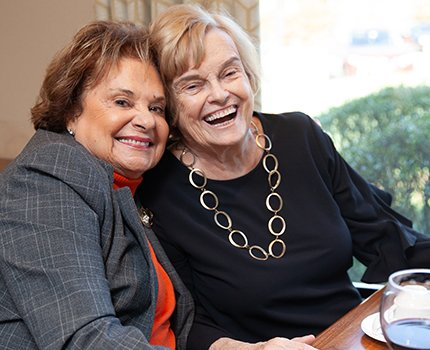 Two women residents enjoying a laugh over lunch in the sophisticated sun porch dining room