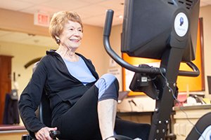 Resident exercising on an incumbent bike in the White Horse Village fitness center
