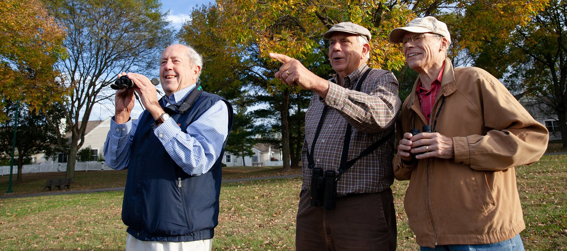 Three men birdwatching and sharing a life around the scenic senior living campus