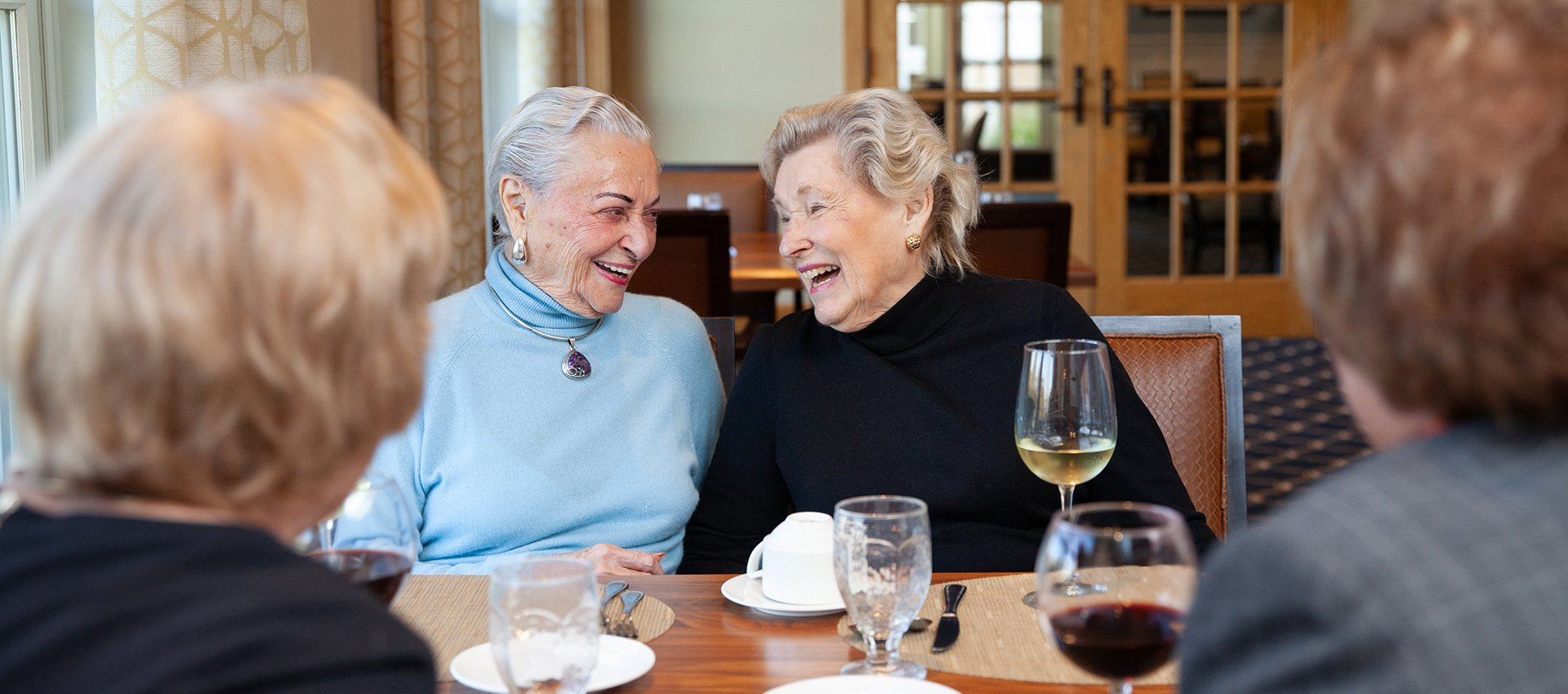 Two independent living residents sharing a laugh over a meal in the Sun Porch Dining