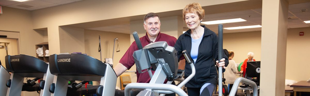 Resident receiving outpatient therapy with a trainer in the beautiful fitness center