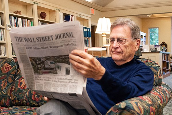 Senior living resident reads the newspaper in the campus library
