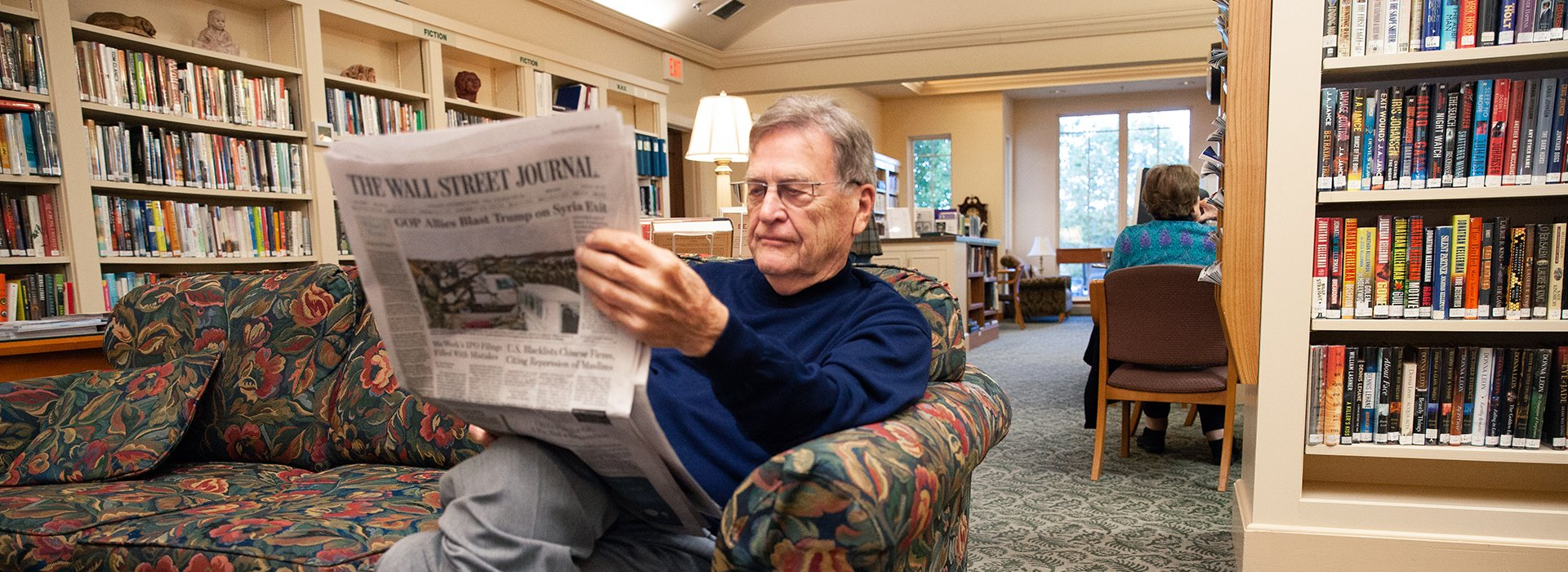Man reading the Wall Street Journal in the state-of-the-art library